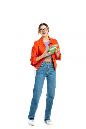 full length of cheerful young student in glasses holding books isolated on white