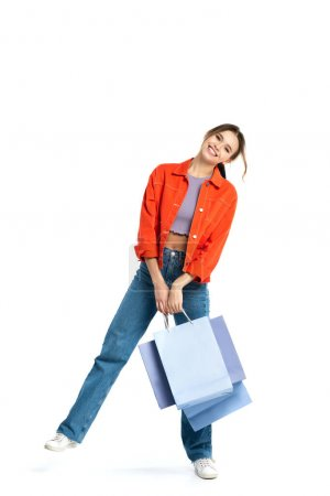 Photo pour Pleine longueur de femme positive en chemise orange tenant des sacs à provisions tout en se tenant isolé sur blanc - image libre de droit