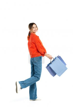 Photo pour Pleine longueur de jeune femme heureuse en chemise orange tenant des sacs à provisions isolés sur blanc - image libre de droit