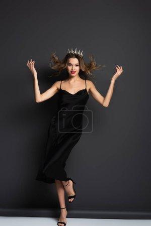 full length of elegant woman in black slip dress and tiara on grey