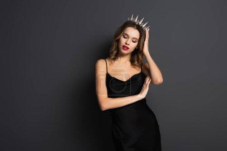 young woman in black slip dress adjusting tiara with diamonds on grey