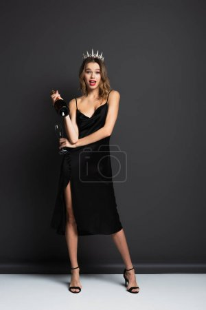 volle Länge der staunenden Frau in schwarzem Slip-Kleid und Diadem mit Diamanten, die Flasche Champagner und Glas auf grau halten