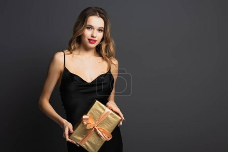 elegant young woman in black slip dress holding wrapped gift box isolated on grey