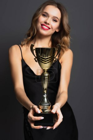 Photo pour Jeune femme heureuse floue en robe noire glissante tenant trophée d'or sur gris - image libre de droit