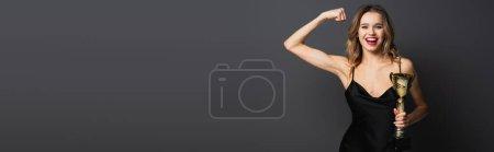 Photo pour Heureuse jeune femme en robe noire glissante tenant trophée d'or et montrant le muscle sur gris, bannière - image libre de droit