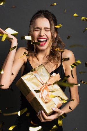 excited young woman in black slip dress holding gift box near blurred confetti on grey