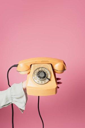Vue recadrée du téléphone vintage en main de femme isolée sur rose
