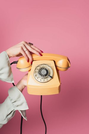 Cropped view of woman holding retro phone isolated on pink