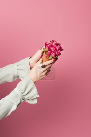 Photo for Cropped view of woman holding waffle cone and flowers in hands isolated on pink - Royalty Free Image