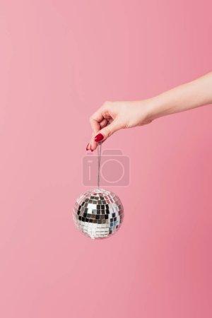 Photo pour Vue recadrée de la femme tenant la boule disco isolée sur rose - image libre de droit