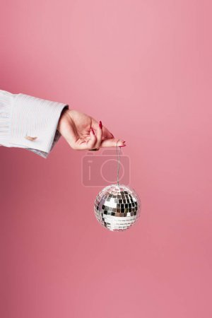 Photo for Cropped view of young woman holding disco ball isolated on pink - Royalty Free Image