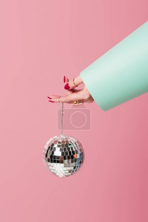 Cropped view of woman with red manicure and accessories holding disco ball isolated on pink