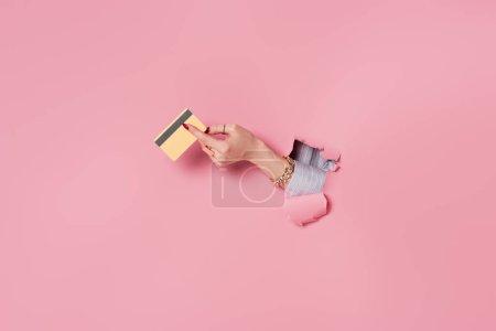 Vista parcial de la tarjeta de crédito en la mano de la mujer cerca de fondo rosa con agujero