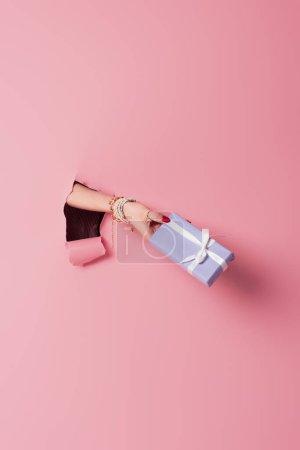 Photo pour Vue recadrée du présent avec arc à la main de la femme près de fond rose avec trou - image libre de droit