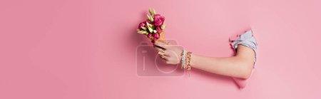 Photo pour Vue recadrée de la femme tenant un délicieux cône de gaufre et des fleurs roses dans un trou de fond rose, bannière - image libre de droit