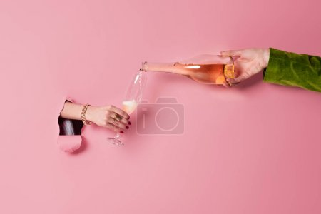 Cropped view of man pouring champagne near woman with glass and pink background with hole