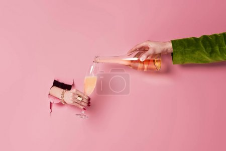 Partial view of woman holding glass near man with bottle of champagne and pink background with hole