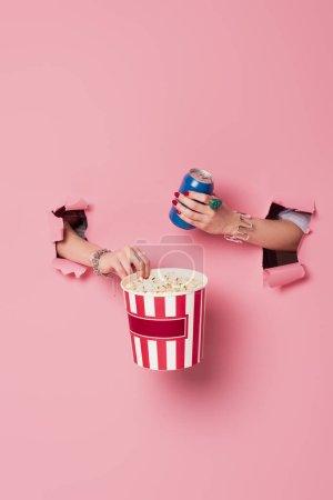 Photo pour Vue recadrée d'une femme tenant du maïs soufflé et buvant dans une boîte près du fond rose avec des trous - image libre de droit