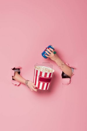 Photo pour Vue recadrée de la femme tenant seau de maïs soufflé et boire près de fond rose avec des trous - image libre de droit