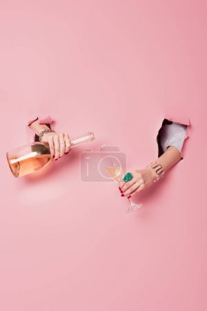 Cropped view of woman pouring champagne near pink background with holes