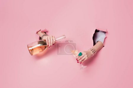 Cropped view of woman pouring champagne in glass in holes of pink background