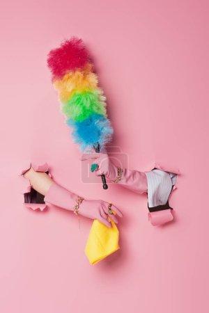 Photo pour Vue recadrée de la femme en gants tenant chiffon et brosse à poussière près de fond rose avec des trous - image libre de droit