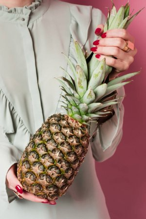 Cropped view of young woman holding exotic pineapple on pink background