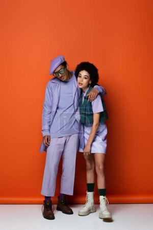 Photo for Full length of trendy african american man smiling while posing with curly woman on orange - Royalty Free Image