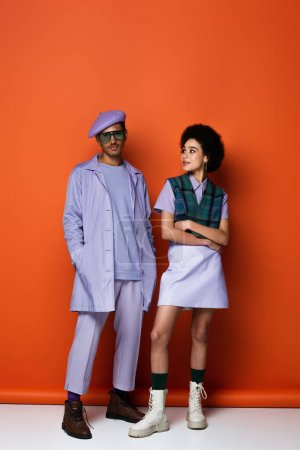 Photo for Full length of trendy african american woman standing with crossed arms and looking at stylish man on orange - Royalty Free Image
