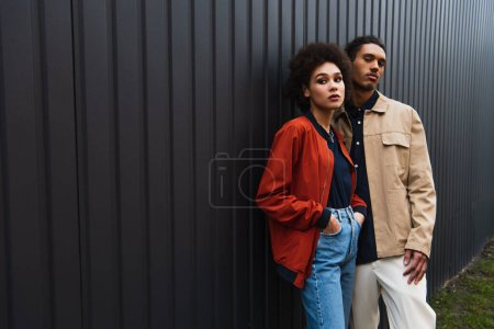 african american man looking at camera while posing with curly woman in jeans outside
