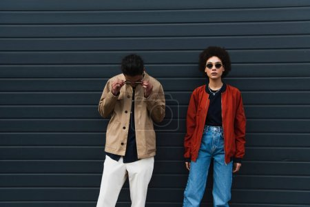 joven afroamericano hombre ajustando gafas de sol y posando con mujer con estilo en jeans fuera