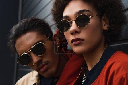 Nahaufnahme eines jungen afrikanisch-amerikanischen Mannes, der mit einer stilvollen Frau mit Sonnenbrille posiert
