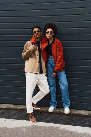 Photo for Full length of young african american woman posing with stylish man in sunglasses outside - Royalty Free Image
