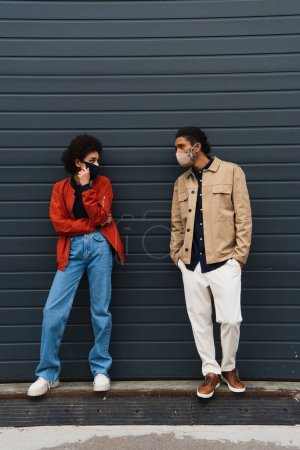 Photo for Full length of trendy young african american couple in protective masks posing outside - Royalty Free Image