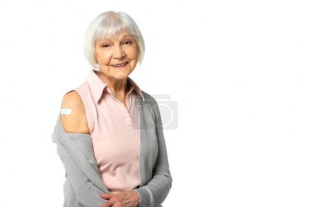 Positive elderly woman with adhesive plaster on arm looking at camera isolated on white