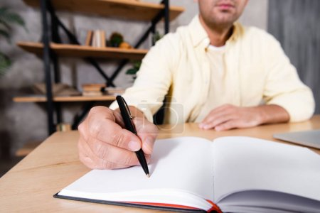 cropped view of freelancer writing in notebook on blurred background