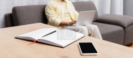 selective focus of notebook and smartphone with blank screen near freelancer on blurred background, banner