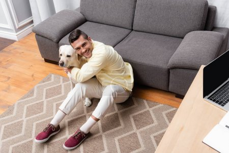 young man smiling at camera while hugging labrador on floor near desk with laptop