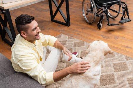 Lächelnder, behinderter Mann streichelt Labrador, während er auf dem Boden in der Nähe des Rollstuhls sitzt