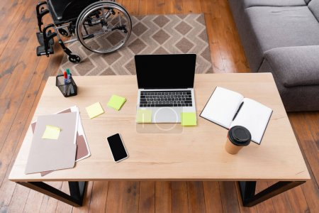 Photo for High angle view of desk with gadgets, documents and takeaway drink near wheelchair - Royalty Free Image