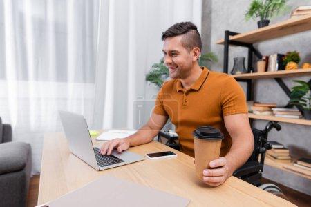 positiver, behinderter Mann mit Kaffee to go beim Tippen auf Laptop neben Handy mit leerem Bildschirm