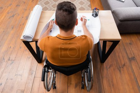 Photo for Overhead view of disabled engineer working near blueprint at home - Royalty Free Image