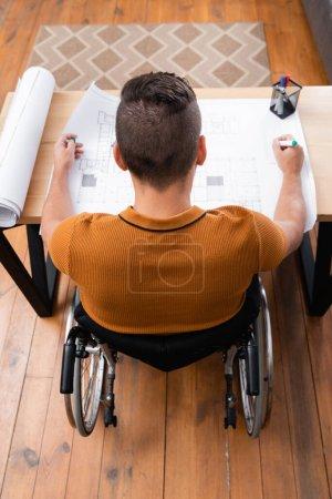 Photo pour Vue aérienne de l'architecte handicapé tenant un stylo feutre tout en travaillant avec le plan à la maison - image libre de droit
