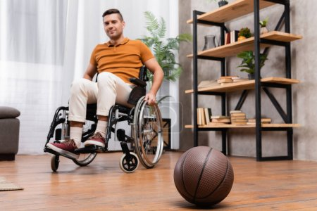 Photo for Selective focus of basketball near young handicapped man sitting in wheelchair - Royalty Free Image