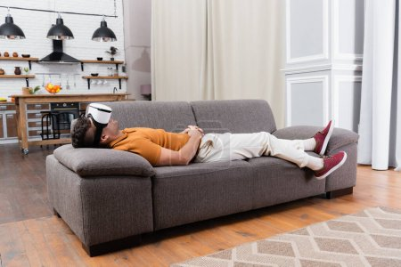 Photo for Young man in casual clothes relaxing in vr headset on sofa at home - Royalty Free Image