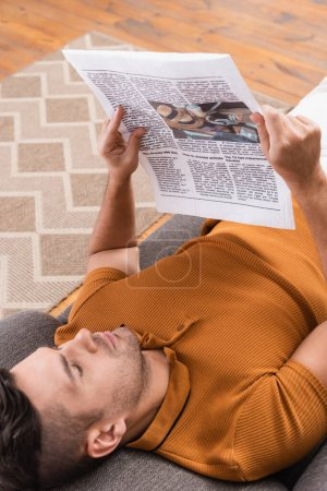 Photo for Overhead view of young man reading newspaper while lying on couch - Royalty Free Image