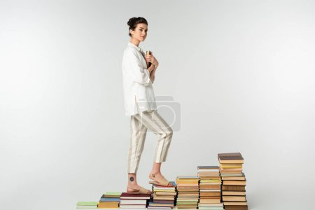 Photo for Full length of young tattooed woman standing on pile of books isolated on white - Royalty Free Image
