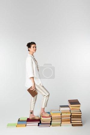 Photo pour Pleine longueur de jeune femme avec tatouage debout sur pile de livres isolés sur blanc - image libre de droit