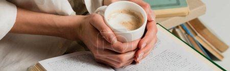 vista recortada de la mujer con libro sosteniendo taza de café aislado en blanco, bandera