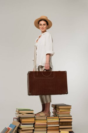 full length of pleased woman in straw hat and glasses holding baggage while standing on pile of books isolated on white
